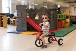 Child wearing sunglasses, looking at camera, sits on red trike in front of big gray plastic castle