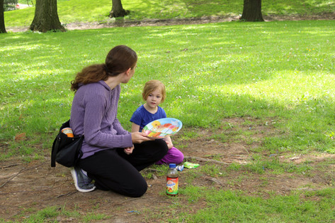 Adult, looking away, kneels on ground with paper plate, next to child, in grass
