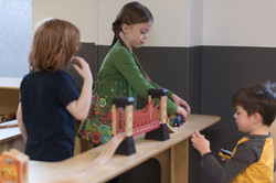 PTLL interior, one child in profile puts together wooden train tracks while another child looks on