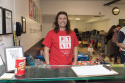 PTLL interior, adult in red PTLL shirt standing behind front desk, smiling at camera
