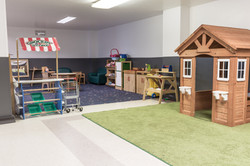 PTLL interior, with wooden playhouse, market, tool bench, kitchen
