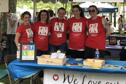 Outdoors at event, five adults in red PTLL shirts standing behind table, smiling at camera