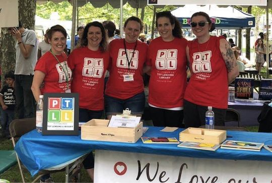 Five adults in red PTLL shirts smile at camera behind our event table