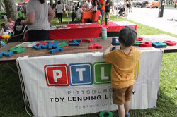 Child, back to camera, looking at large foam letters at PTLL event table
