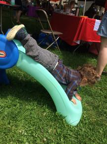 Child slides down blue plastic slide on stomach
