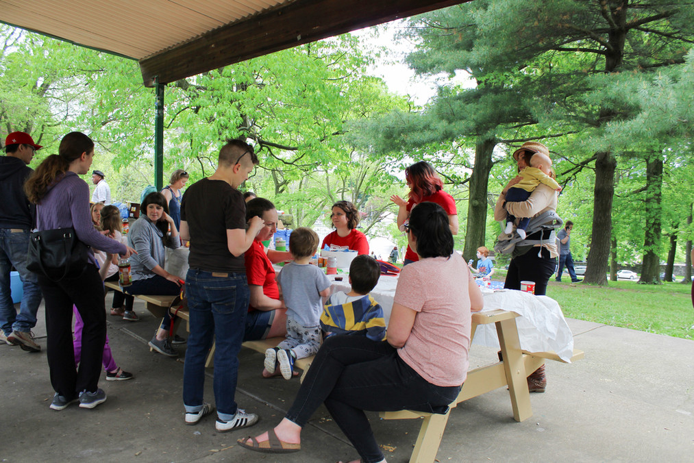 Group shot of adults and children, sitting, standing, talking, and eating at picnic table