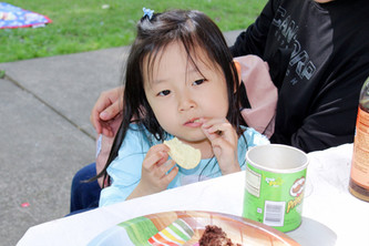 Child sits at picnic table, Pringle in one hand and other hand in mouth