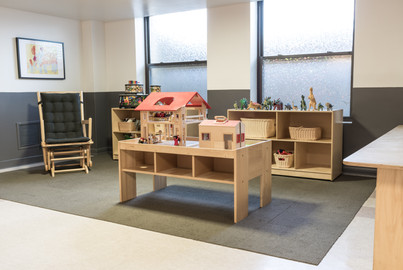 PTLL interior, table with wooden dollhouse, shelves of toys, rocking car