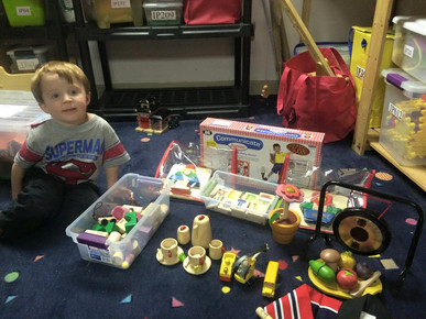 Child looks at camera, next to blocks, tea set, and other toys