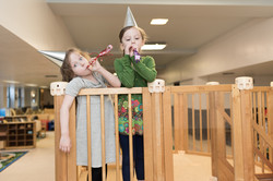 Two children standing on wooden structure. wearing party hats, blowing noise-makers
