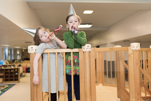 Two children standing on wooden structure, wearing party hats and blowing noisemakers