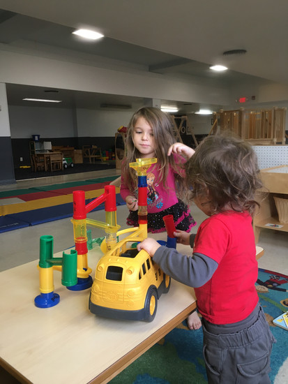 Two children stand at table, playing with marble run, one holds a yellow bus