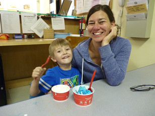 Adult and child, both smiling, sit at an indoor table with cups of ice cream