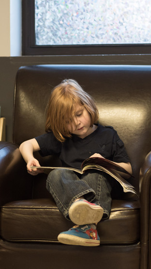 Child sitting on large brown chair, looking down and reading a book