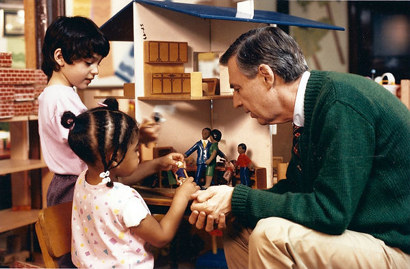 Still from Mr. Rogers episode, Mr. Rogers and two children play with a wooden dollhouse