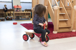 PTLL interior, child sits on wooden balance trike, looks away from camera