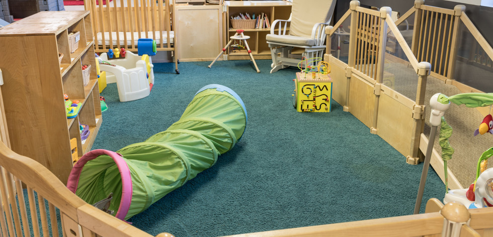 PTLL interior, gated infant area, showing a shelf of toys and play tunnel