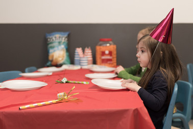 Child sits at table wearing party hats, paper plates and noisemaker on table