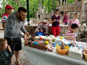 Adults and children at picnic, standing, talking, eating, one adult gets cake for a child