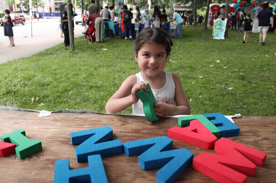 Child holds green foam R, smiles at camera behind event table with other foam letters