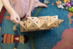 Overhead shot of tower built from wooden magnetic tiles, with child's hand adding a piece