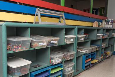 PTLL interior, art room shelves containing bins of supplies and stacks of paper