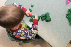 Overhead shot of child cutting green play-dough into small pieces
