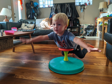 At home, child balances on stomach on the top handle of Playskool sit and spin toy