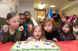 Group of children wearing party hats, huddled around cake as two children in center blow out candles