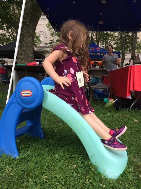 Child slides down blue plastic slide