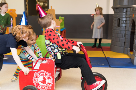 One children in party hat rides a trike with a back platform while two children push