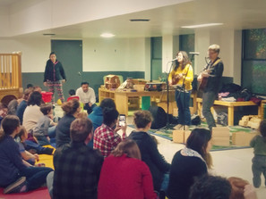Two adults with instruments sing in microphones to crowd of sitting adults and children