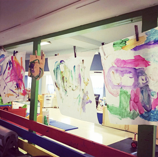 PTLL interior, window of art room, four children's paintings hang on a clothesline to dry