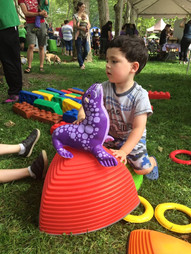 Outdoors, child looks to side while sitting behind a tall Gonge riverstone with a foam seal atop it