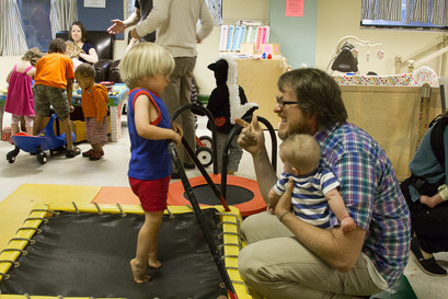 Indoors, adult in profile holding baby while crouching down talking to toddler who's on a trampoline