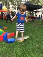 Toddler outdoors, in grass, looking down and standing on monkey balance board