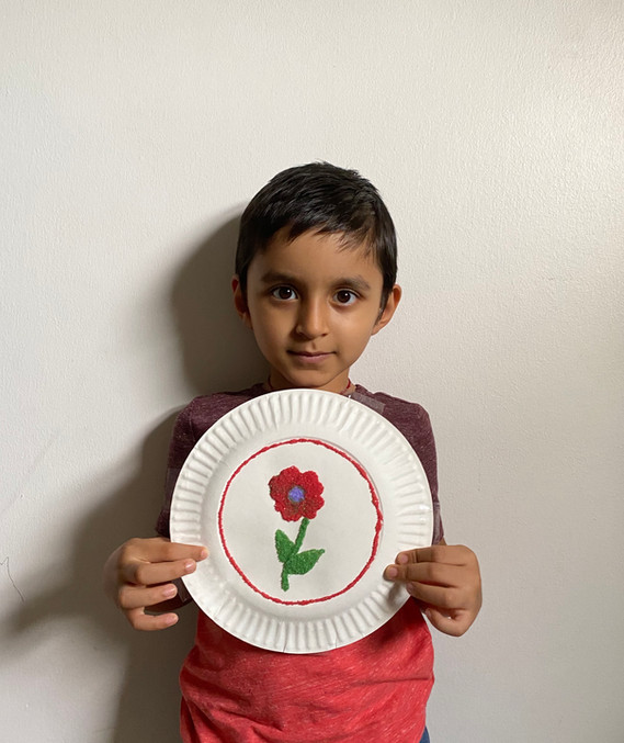 Child standing against wall, looking at camera, holding paper plate with flower drawn on it