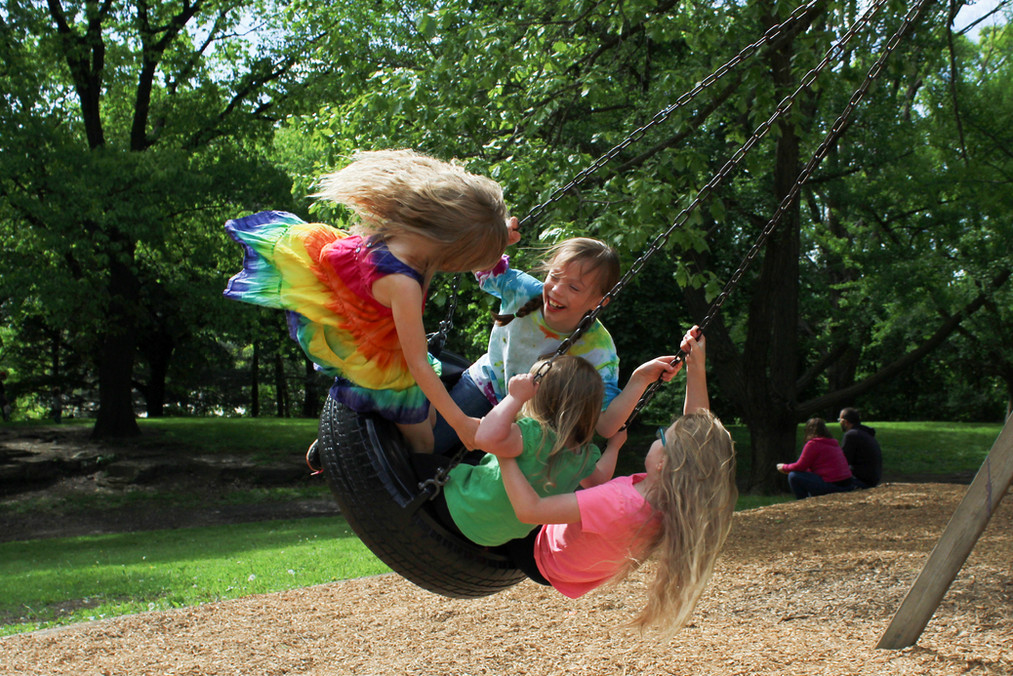 Four children in mid-air, swinging on tire, one looking at camera and smiling