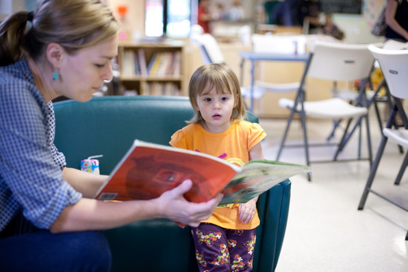 Indoors, adult holds out a book and reads to child