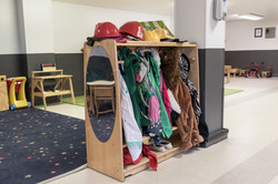 PTLL interior, showing a rack with a mirror that holds dress-up clothes and hats