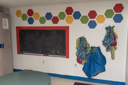 Art room, with cabinet, table, chalkboard, and smocks hanging on wall