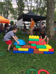 Two children, in profile, build with large plastic blocks and riverstones