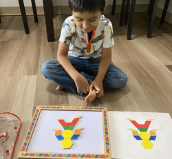 Child sits on floor and looks down at Magnetic Pattern Blocks that make a picture of a person