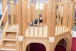 PTLL interior, toddler in crawling position looks through slats in wooden climber
