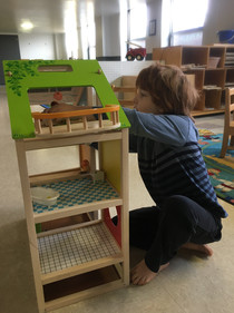 One child sits on floor playing with wooden dollhouse