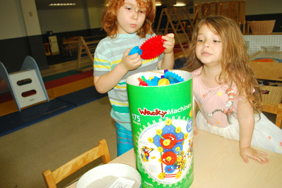 Two children look at Superstructs Wacky Machines, pulling one out and looking into canister