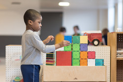 Child builds a structure with colorful magnetic tiles