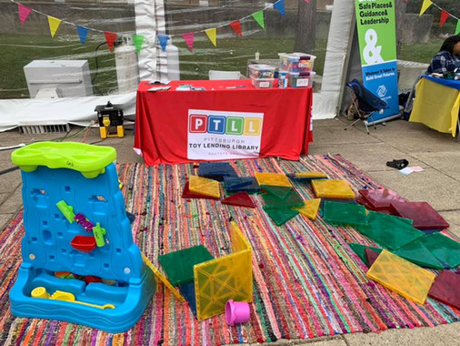 PTLL event table set up next to rug with a water toy and jumbo-size magnetic tiles
