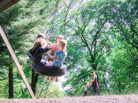 Four children swing on tire. Adult and child in background. Saturated green of trees behind them