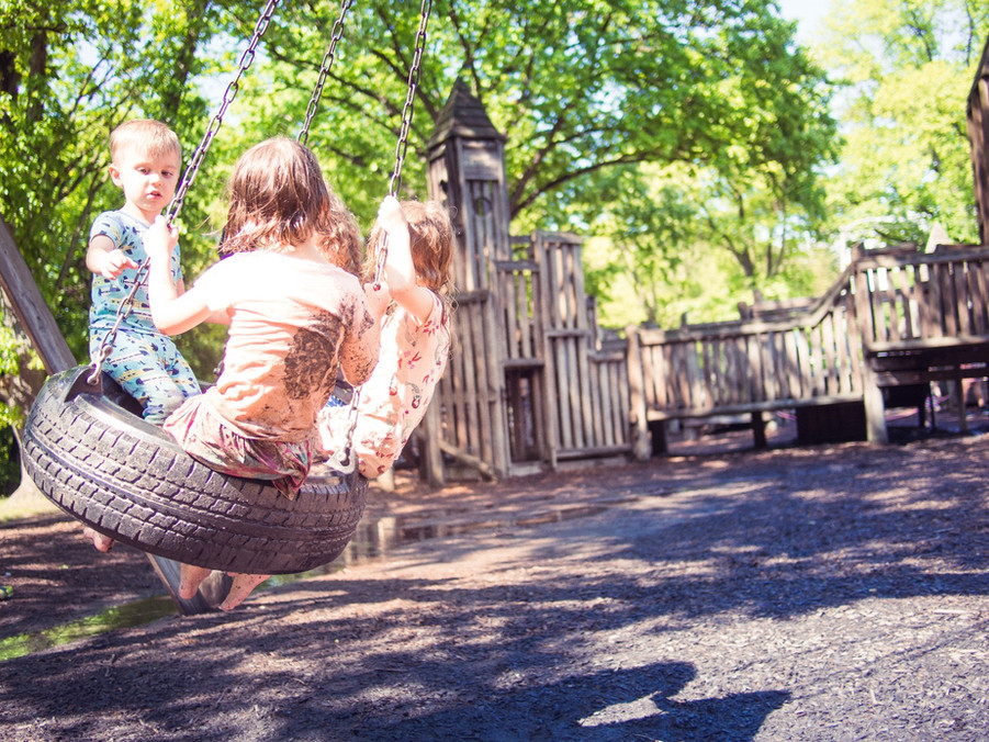 Three children swing on tire, wooden castle playground and trees behind them